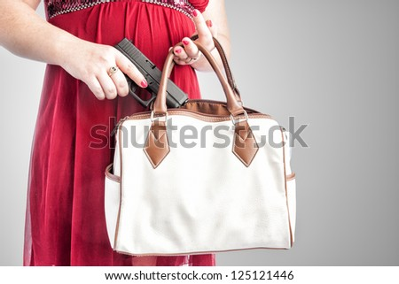 White woman in a red dress removing a small handgun from her purse. Conceal carry weapon for protection. Focus from the knees to the neck so it could be used for many ages. - stock photo