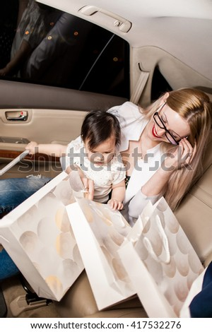 White woman with a child of one year in the light leather car interior look at the present