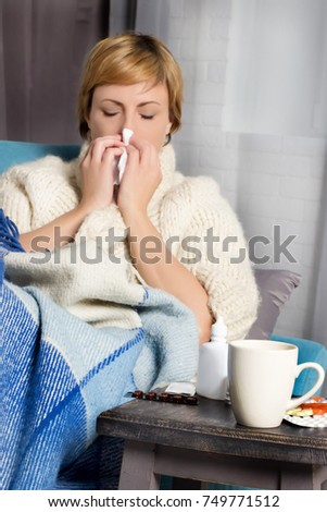White woman with short hair in warm winter clothes at home blowing her nose in tissue with pills and medicine. Sickness, allergies concept.