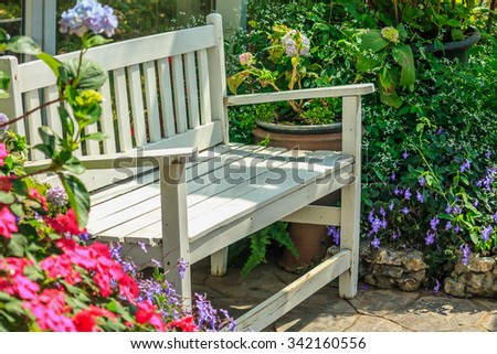 white wood chair in the flowers garden