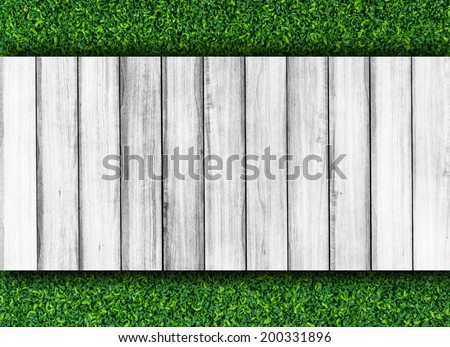 White wood wall on green grass texture background.