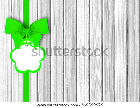 white wooden background with beautiful green bow with tag - stock photo