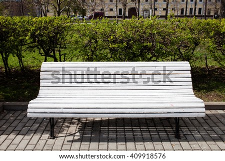 White wooden bench in the park - stock photo