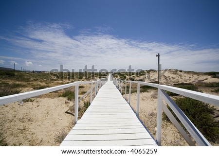 white wooden boardwalk in the beach - stock photo