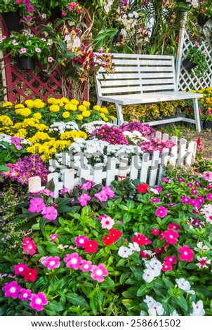 White wooden chair in the flowers garden. Flowers in the garden. - stock photo