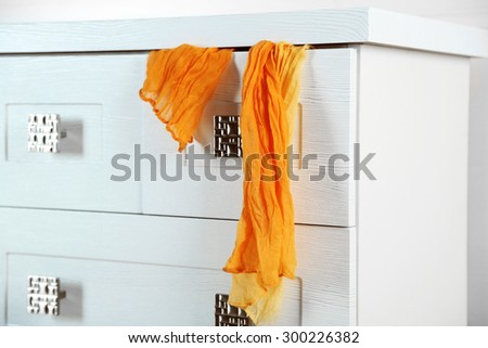 White wooden chest of drawer with scarf in opened drawer  - stock photo