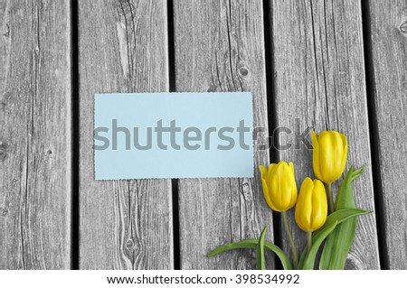 White wooden floor with 3 tulips and postcard teal - stock photo