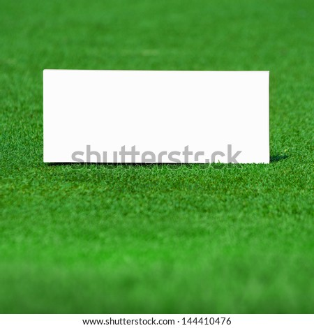 White wooden sign on green grass background - stock photo
