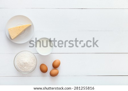White, wooden table top view. On the table are perfect food, spaghetti, flour, cheese, eggs to cook a delicious breakfast. - stock photo