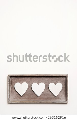 White wooden vintage background with three hearts. - stock photo