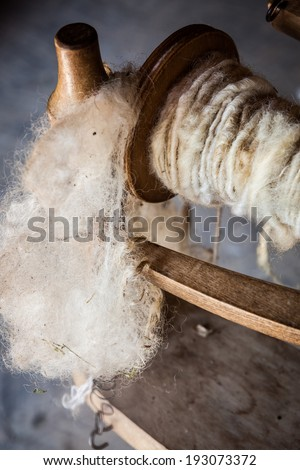 White wool and yarn on old fashioned spinning wheel