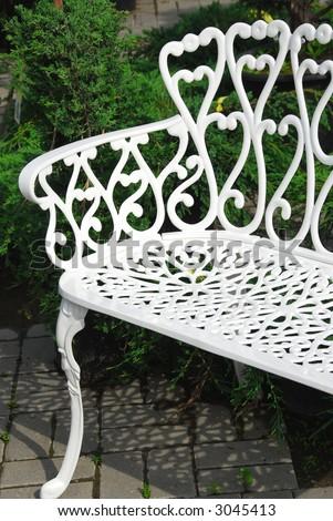 White wrought iron bench in a garden - stock photo