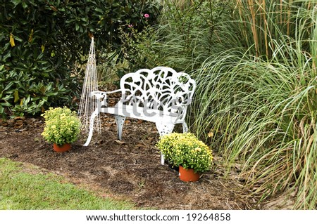 White wrought iron bench in a garden setting surrounded by fall mums - stock photo
