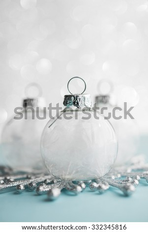 White xmas ornaments on glitter bokeh background. Merry christmas card. Winter holiday theme.