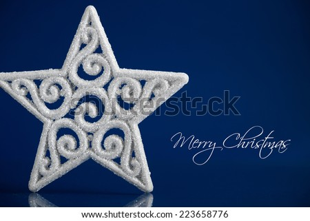 White xmas star on dark blue christmas background with space for text. Merry christmas card. - stock photo