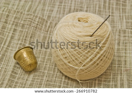 white yarn with needle and thimble on fabric  - stock photo