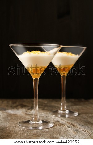 White yogurt with gold honey in a glass. Traditional greek dessert. Light healthy natural dietetic snack or meal. Stone background, top view, copy space