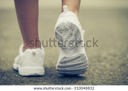 White youth sneakers on girl legs on road during sunny  summer day. - stock photo