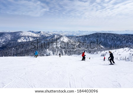 WHITEFISH, MONTANA-MARCH 24: Skiers descend from the summit at Whitefish Mountain Resort March 24, 2014. At a summit elevation of 6,817ft, Glacier National Park is visible at a distance on this day. - stock photo