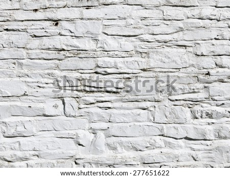 Whitewashed paint on stone wall close up. - stock photo
