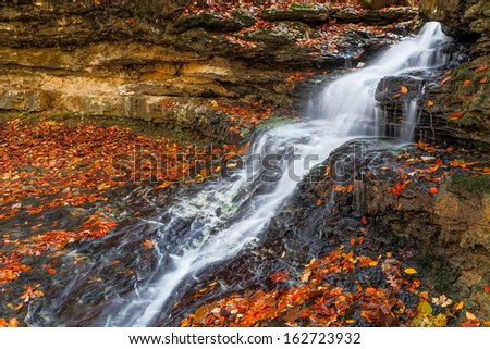 Whitewater cascades down rock ledges of a small waterfall with vividly colorful autumn leaves all around. Shot near the dam at Cagle's Mill Lake, Indiana. - stock photo