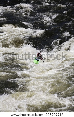 Whitewater Kayaker Maneuvering Through Rapids
