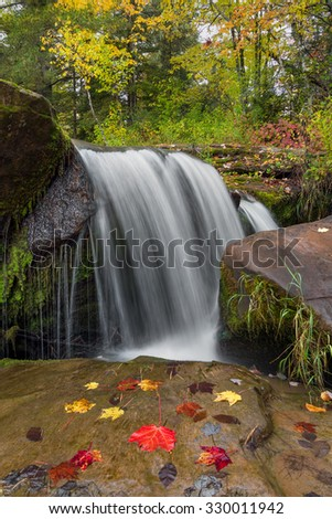 Whitewater plunges over a  rock ledge with colorful autumn leaves at the upper cataract of O Kun De Kun Falls, a waterfall in the scenic Upper Peninsula of Michigan. - stock photo