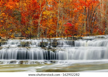 Whitewater pours over rock ledges at Indiana's Upper Cataract Falls with beautiful, colorful fall foliage. - stock photo