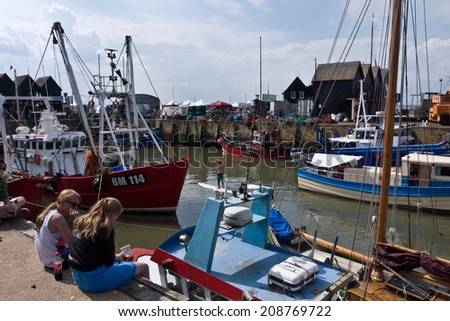 WHITSTABLE, UK-JULY 27: Visitors and boat owners enjoy the Harbour at Whitstable where thousands of visitors attend the annual Whitstable Oyster Festival. July 27, 2014 , Whitstable Kent UK.  - stock photo