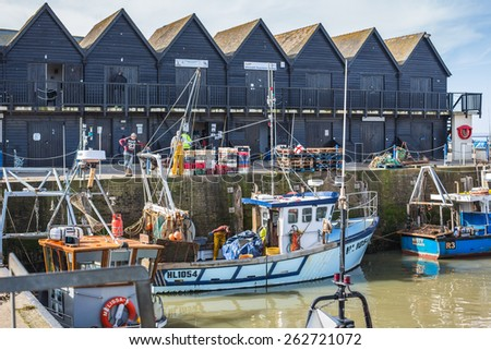 WHITSTABLE, UK - MARCH 10, 2015: Fishermen examine and deal with their latest catch in Whitstable harbour. The harbour was built by the Canterbury and Whitstable Railway Company in 1832. - stock photo