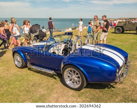 Whitstable, UK, 2nd August 2015. A blue vintage AC Cobra  sports car is on display for visitors to Tankerton slopes to enjoy during the classic car motor show in Whitstable, Kent. - stock photo