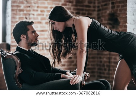Who set the rules? Beautiful young woman in cocktail dress leaning to her boyfriend sitting in chair while looking at each other in loft interior - stock photo