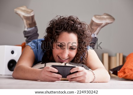 who the hell said that girls don't play videogames? Of course they do it, and they do it the most on their mobile phones - stock photo