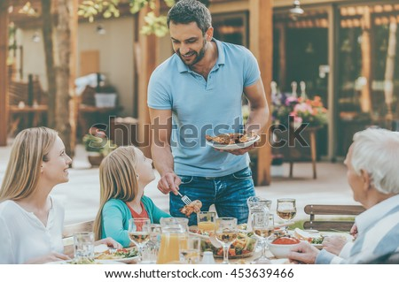 Who wants some chicken? Happy family of five people communicating and enjoying meal together while sitting at the dining table in formal garden - stock photo