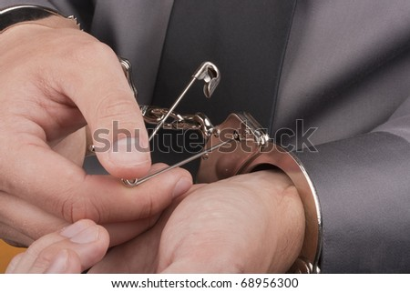 Who was arrested trying to break free from the handcuffs with the pin. - stock photo