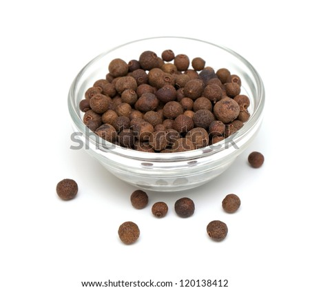 whole allspice berries in a glass bowl over white