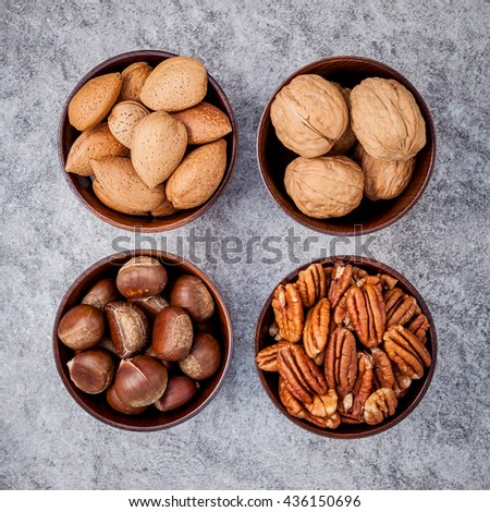 Whole almonds,whole walnuts ,whole hazelnut and pecan nuts in wooden bowl setup with stone background.