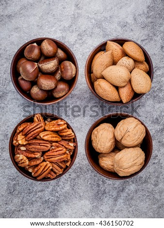 Whole almonds,whole walnuts ,whole hazelnut and pecan nuts in wooden bowl setup with stone background.   - stock photo