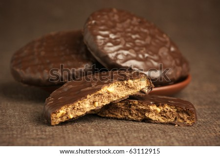 Whole and break chocolate cookies on brown canvas.