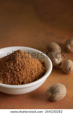 Whole and ground nutmeg a fragrant spice from the fruit of Myristica fragrans tree indigenous to the Banda Islands of Indonesia - stock photo