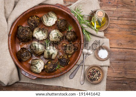 Whole and half artichokes roasted simply, served with olive oil, pepper and salt on the wooden table. Top view. - stock photo