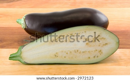 Whole and Half Cut Eggplants on Wood Table - stock photo