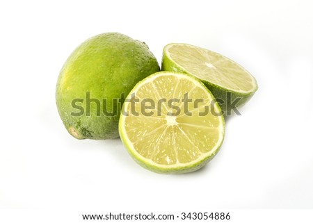 Whole and half cut lime fruits isolated on white