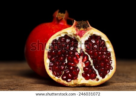 Whole and half-cutted pomegranate on rustic wooden table - stock photo
