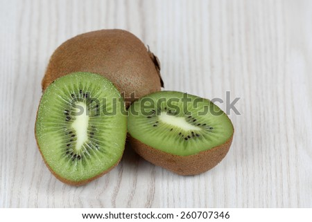 Whole and sliced fruits on table - cut in half kiwi green pulp - diet, nutrition and natural vitamins concept - stock photo