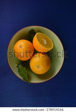 Whole and sliced oranges with leaf in a green bowl on blue background. Top angle shot. - stock photo