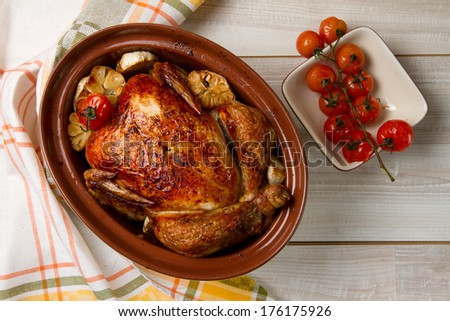 Whole baked chicken with garlic and cherry tomatoes - stock photo