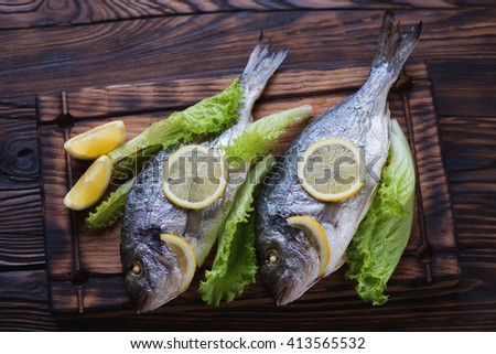 Whole baked dorado fish with salad in a rustic wooden setting - stock photo