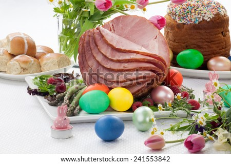 Whole baked honey sliced ham with fresh raspberry, asparagus, dyed Ester eggs, Easter cake, and cross buns. Spring flowers.  - stock photo
