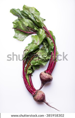 whole beetroots with green leaves, isolated on a white background, top view, vertical - stock photo